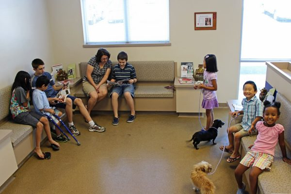 A group of multicultural children sitting on a bench in the waiting room reading books and playing with their dogs
