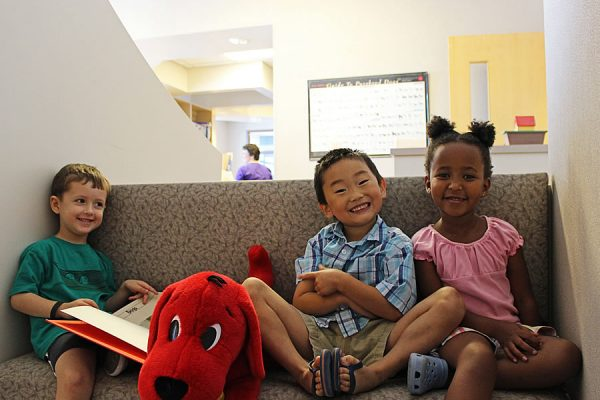 A group of multicultural children sitting on a bench in the waiting room reading books and playing with a Clifford the Big Red Dog toy
