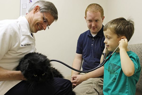 Dr. Denny letting a small boy listen to his black cats heart through a stethoscope while his dad looks on