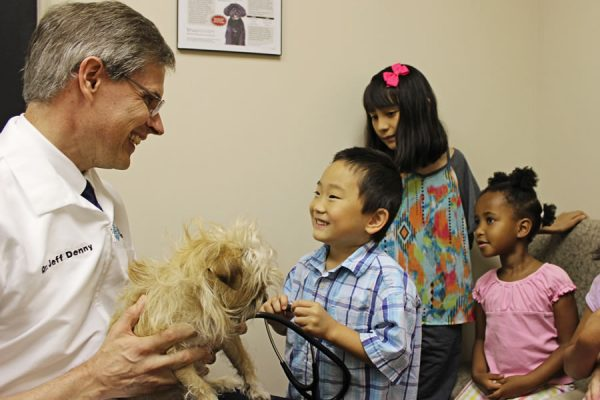 Dr. Denny showing a scruffy tan dog to a group of multi cultural children