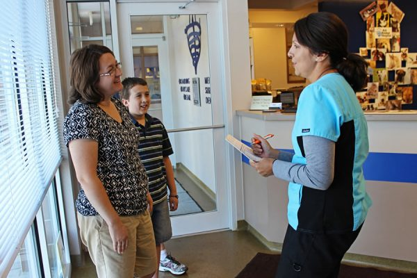 A team member speaking with a client and her son in the front lobby of the clinic