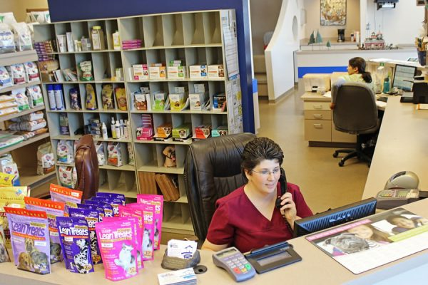 A team member answering the phone at the front desk. Also pictured is the pet food display